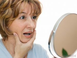 older-woman-looking-in-mirror-with-hand-on-chin